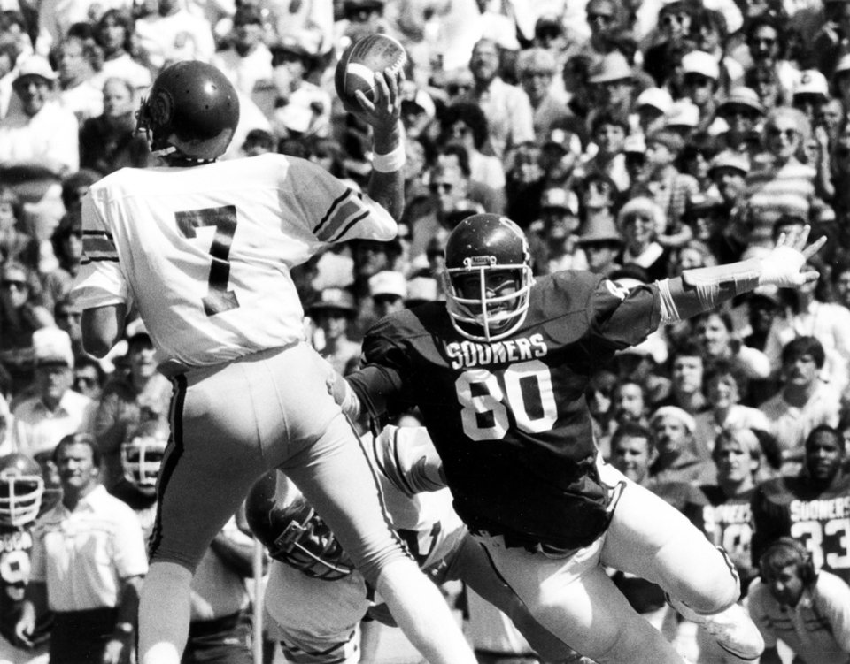 University of Oklahoma defenseman Rick Bryan (80) puts some pressure on Southern Cal quarterback Sean Salisbury (7), but the Trojan QB still completed a first quarter pass play. Southern Cal went on to defeat the Sooners, 12-0. Staff photo by Jim Argo taken 9/25/82.