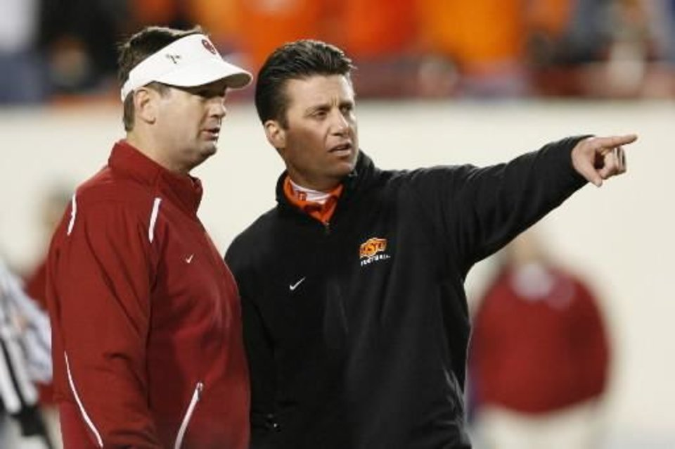 OU head coach Bob Stoops, left, and OSU head coach Mike Gundy talk before the game during the first half of the college football game between the University of Oklahoma Sooners (OU) and Oklahoma State University Cowboys (OSU) at Boone Pickens Stadium on Saturday, Nov. 29, 2008, in Stillwater, Okla. STAFF PHOTO BY NATE BILLINGS