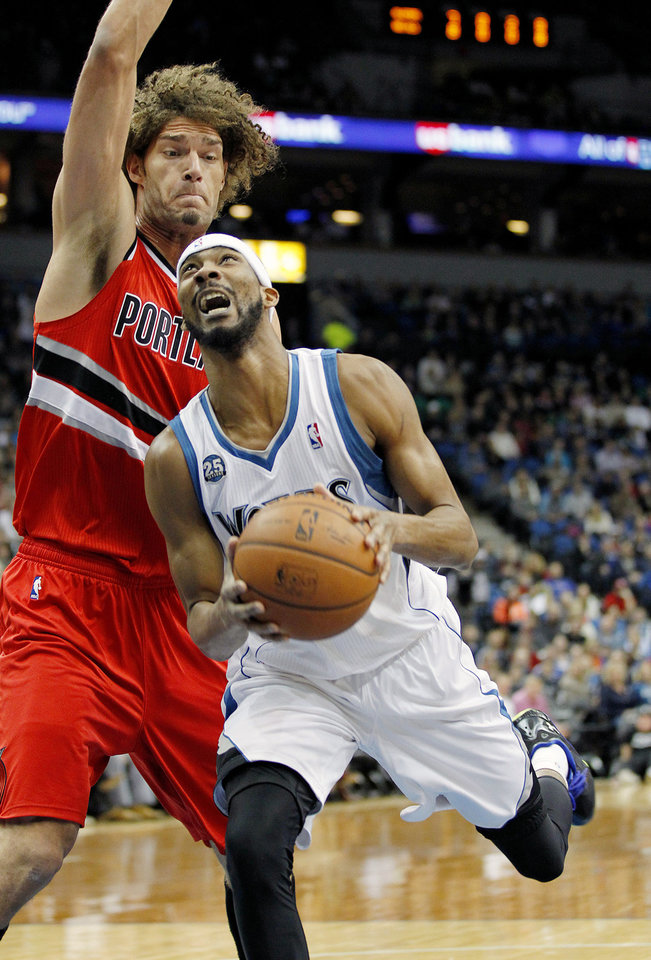 Photo - Minnesota Timberwolves Corey Brewer drives on Portland Trail Blazers Robin Lopez in the first quarter of their NBA basketball game on Saturday, Feb. 8, 2014 in Minneapolis.(AP Photo/Andy Clayton-King)