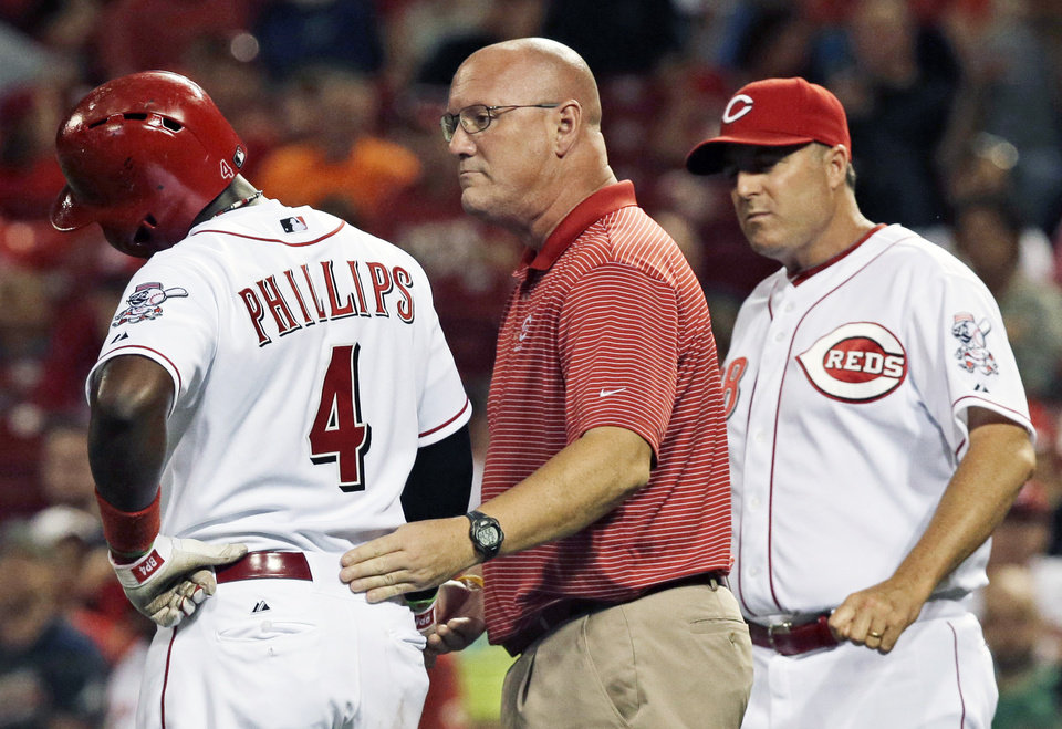 Photo - Brandon Phillips (4) is checked by trainer Paul Lessard after Phillips was hit in the hand by a pitch from Atlanta Braves starting pitcher Ervin Santana in the fourth inning of a baseball game, Saturday, Aug. 23, 2014, in Cincinnati. Manager Bryan Price comes to check at right. Phillips stayed in the game. (AP Photo/Al Behrman)