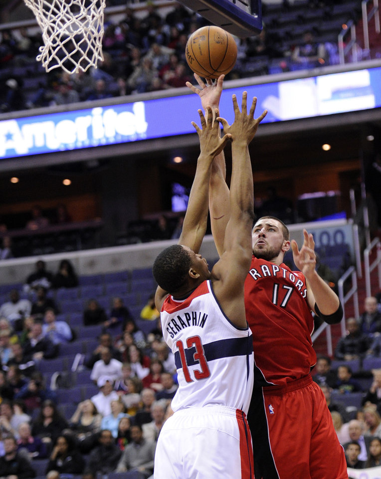 Photo - Toronto Raptors center Jonas Valanciunas (17), of Lithuania, goes to the basket as he is fouled on the play by Washington Wizards forward Kevin Seraphin (13), of France, during the first half of an NBA basketball game, Sunday, March 31, 2013, in Washington. (AP Photo/Nick Wass)