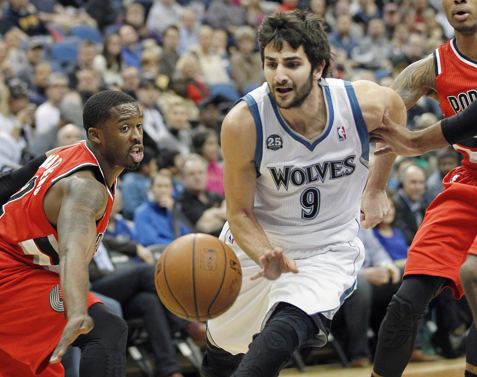 Photo - Minnesota Timberwolves guard Ricky Rubio (9) squeezes through pressure defense by Portland Trail Blazers Wesley Matthews,left, in the first quarter of their NBA basketball game on Saturday, Feb. 8, 2014 in Minneapolis.(AP Photo/Andy Clayton-King)
