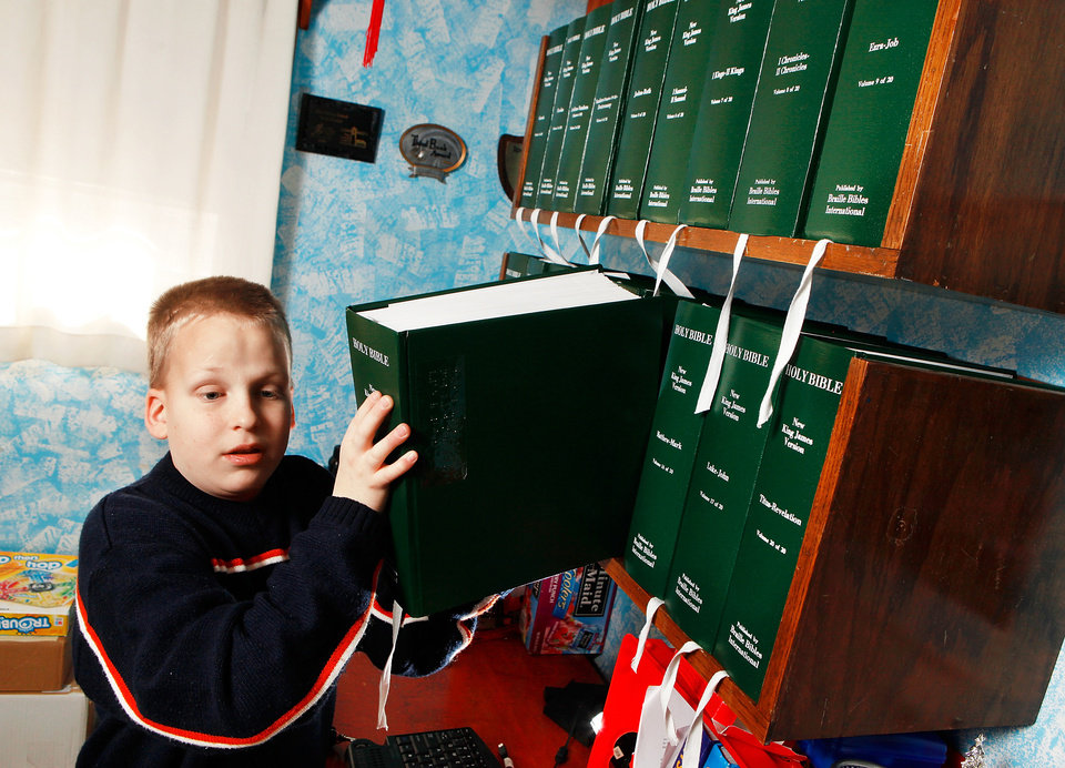 Daniel Brookshire pulls down one of the volumes of his Braille Bible in his family's home in Tulsa.  Photo by JIM BECKEL, tHE OKLAHOMAN