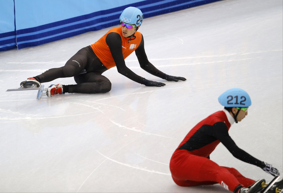 Photo - Wu Dajing of China, right, and Freek van der Wart of the Netherlands crash out in the men's 5000m short track speedskating relay final at the Iceberg Skating Palace during the 2014 Winter Olympics, Friday, Feb. 21, 2014, in Sochi, Russia. (AP Photo/Vadim Ghirda)