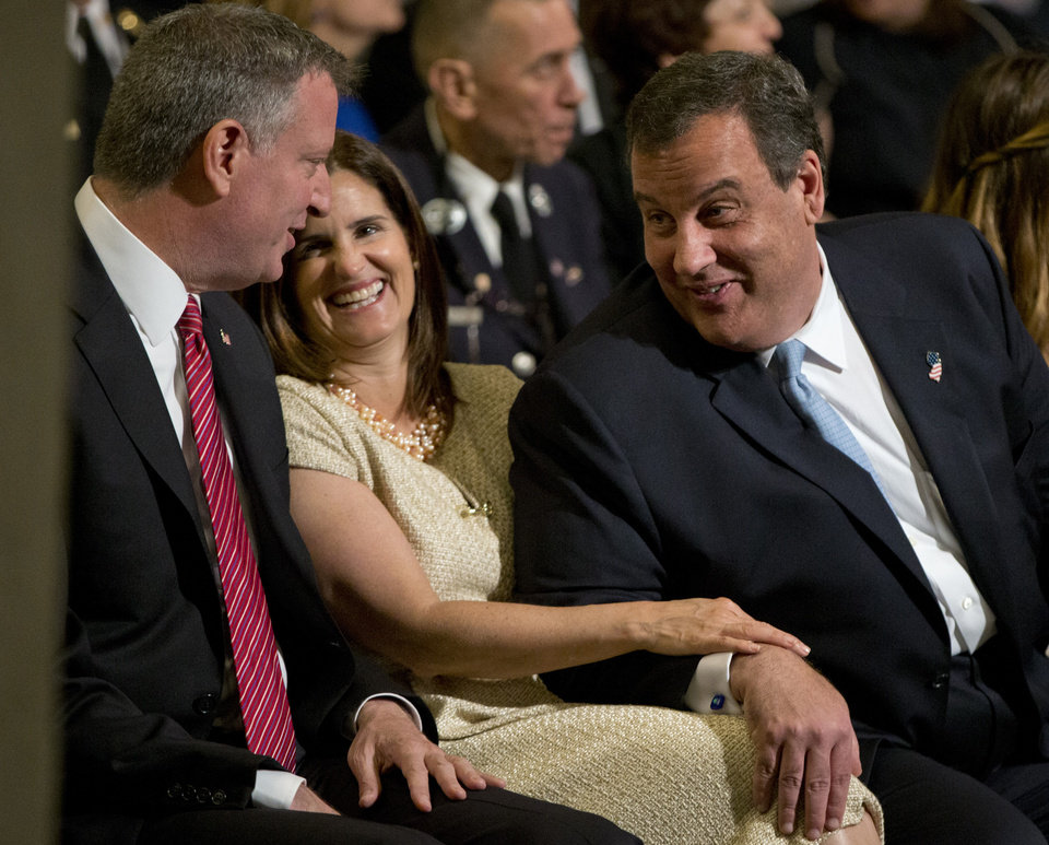 Photo - New York City Mayor Bill de Blasio, left, talks with New Jersey Gov. Chris Christie, right, and his wife Mary Pat Foster, before a ceremony at the National September 11 Memorial Museum, Thursday, May 15, 2014, in New York. The museum is a monument to how the Sept. 11 terror attacks shaped history, from its heart-wrenching artifacts to the underground space that houses them amid the remnants of the fallen twin towers' foundations. It also reflects the complexity of crafting a public understanding of the terrorist attacks and reconceiving ground zero.  (AP Photo/Carolyn Kaster)
