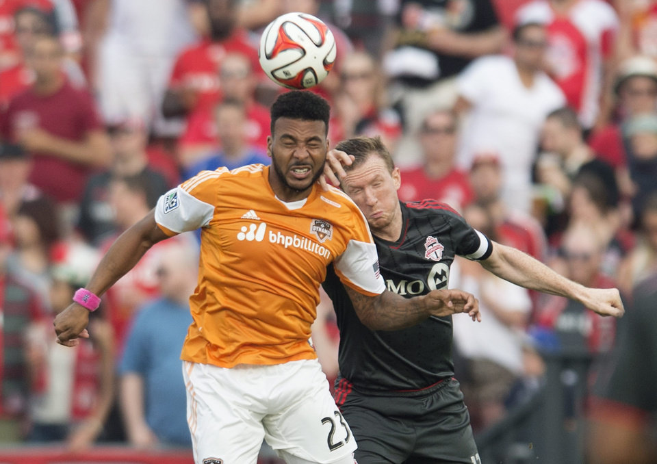 Photo - Houston Dynamo's Giles Barnes, left, and Toronto FC's Steven Caldwell battle for the ball during the first half of MLS soccer action in Toronto on Saturday, July 12, 2014. (AP Photo/The Canadian Press, Darren Calabrese)