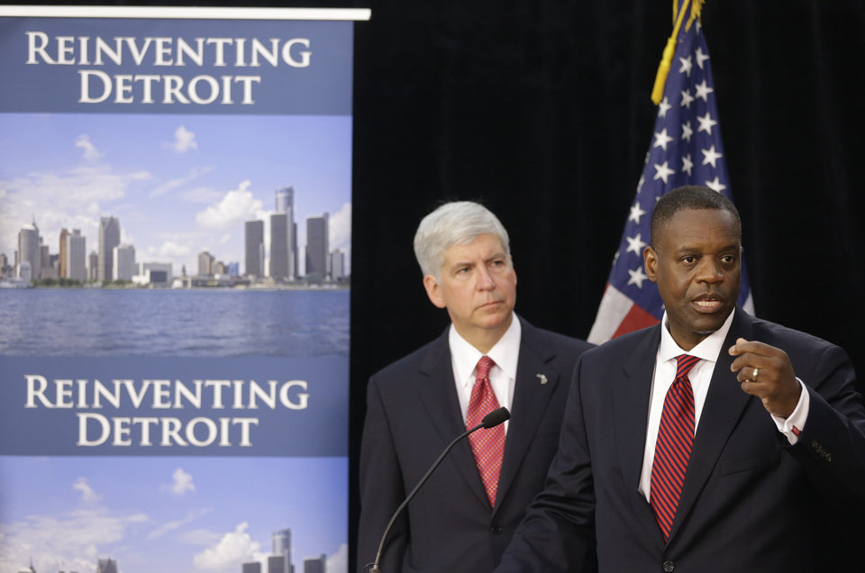 Photo - FILE - In this July 19, 2013, file photo, state-appointed emergency manager Kevyn Orr, right, and Michigan Gov. Rick Snyder, address reporters during a news conference in Detroit after Orr asked a federal judge for bankruptcy protection. Orr chose bankruptcy over diverting money from police, fire and other services to make debt payments. The move conserves cash so the city can operate, but it will hurt Detroit's image for years. It will also leave creditors with much less than they are owed and places in jeopardy the pension benefits of thousands of city retirees. (AP Photo/Carlos Osorio, File)