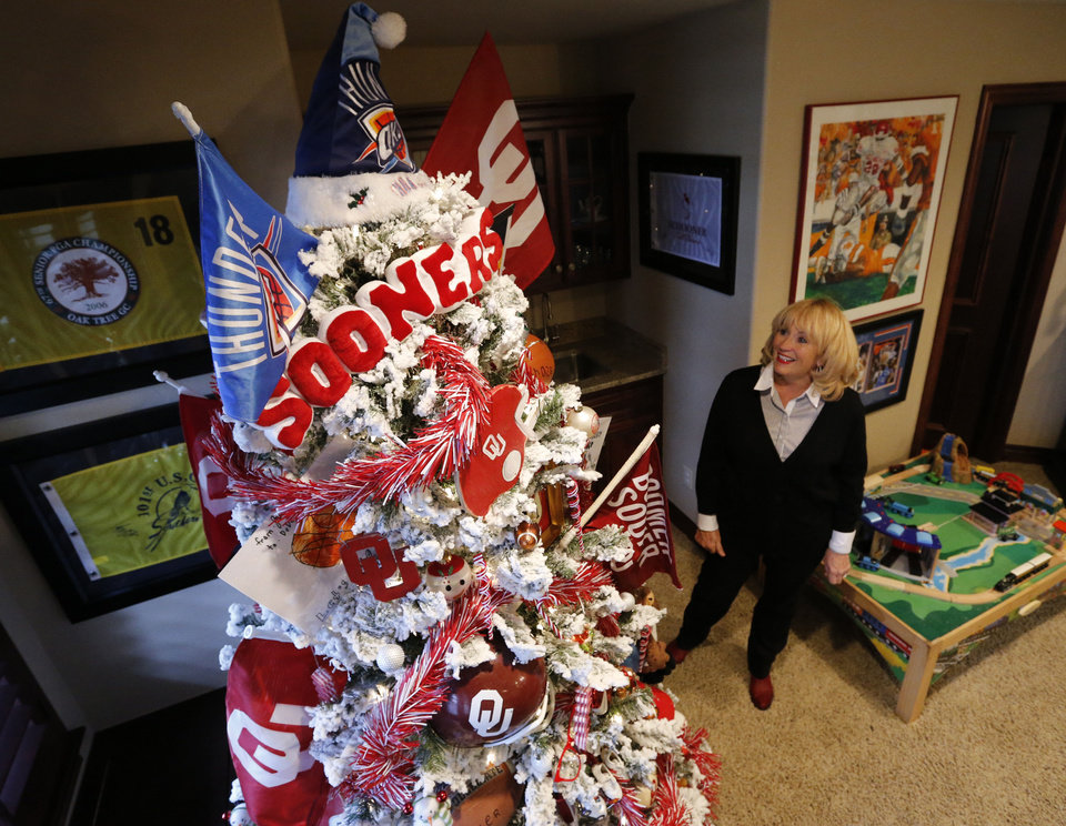Photo - Debbie McCurdy shows off her Christmas tree inspired by the University of Oklahoma Sooners. The McCurdy home is one of five that are on the Assistance League of Norman's Holiday Home Tour. PHOTO BY STEVE SISNEY, THE OKLAHOMAN  STEVE SISNEY
