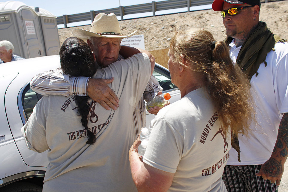 Photo - Rancher Cliven Bundy, second from left, hugs a supporter before holding a news conference near Bunkerville, Nev., Thursday, April 24, 2014. Bundy, a Nevada rancher who became a conservative folk hero for standing up to the government in a fight over grazing rights, lost some of his staunch defenders Thursday after wondering aloud whether blacks might have had it better under slavery. (AP Photo/Las Vegas Review-Journal, John Locher)