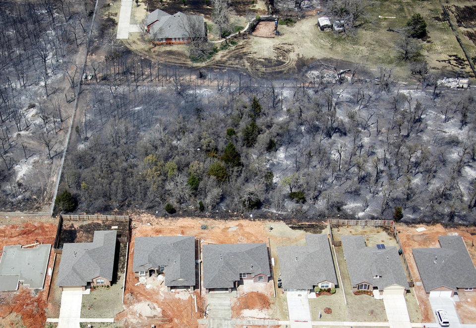 A line of undamaged homes is shown in Midwest City Friday near homes that were destroyed by fires. Photo by Bryan Terry, The Oklahoman