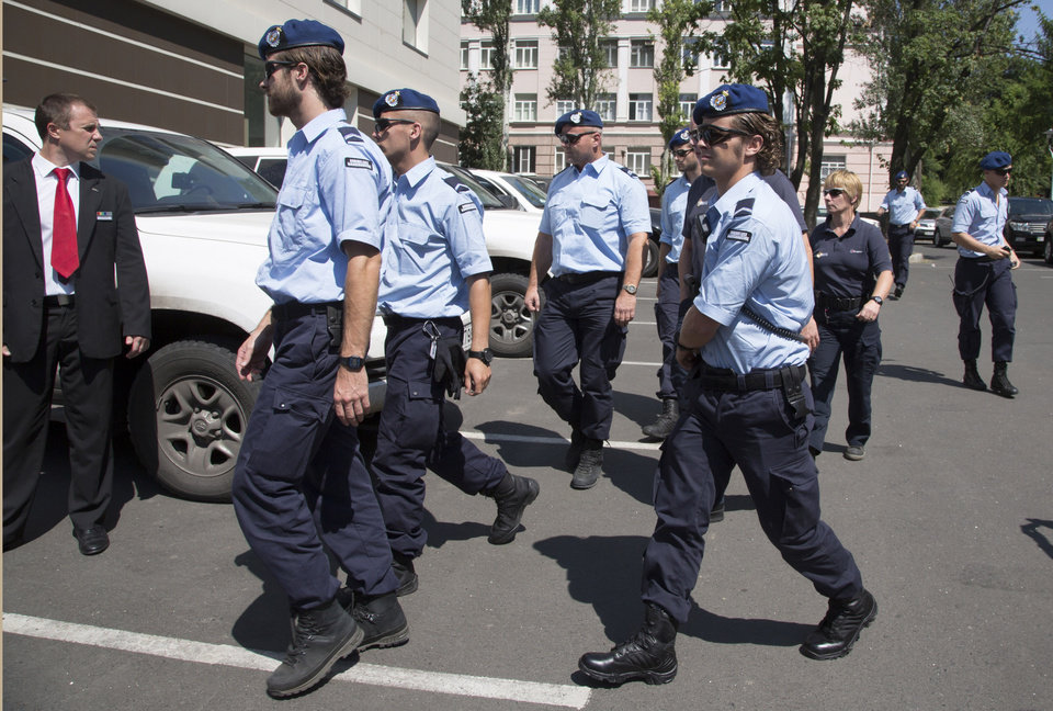Photo - Dutch policemen walk in the city of Donetsk, eastern Ukraine Sunday, July 27, 2014. A team of international police officers that had been due to visit the site of the Malaysian plane disaster in eastern Ukraine cancelled the trip Sunday after receiving reports of fighting in the area. Alexander Hug, the deputy head of a monitoring team from the OSCE in Europe, said it would be too dangerous for the unarmed mission to travel to the site from its current location in the rebel-held city of Donetsk. (AP Photo/Dmitry Lovetsky)