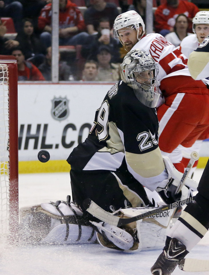 Photo - Pittsburgh Penguins goalie Marc-Andre Fleury (29) and Detroit Red Wings' Niklas Kronwall (55), of Sweden, watch the puck shot by Detroit Red Wings' Gustav Nyquist go into the goal during the second period of an NHL hockey game Thursday, March 20, 2014, in Detroit. (AP Photo/Duane Burleson)