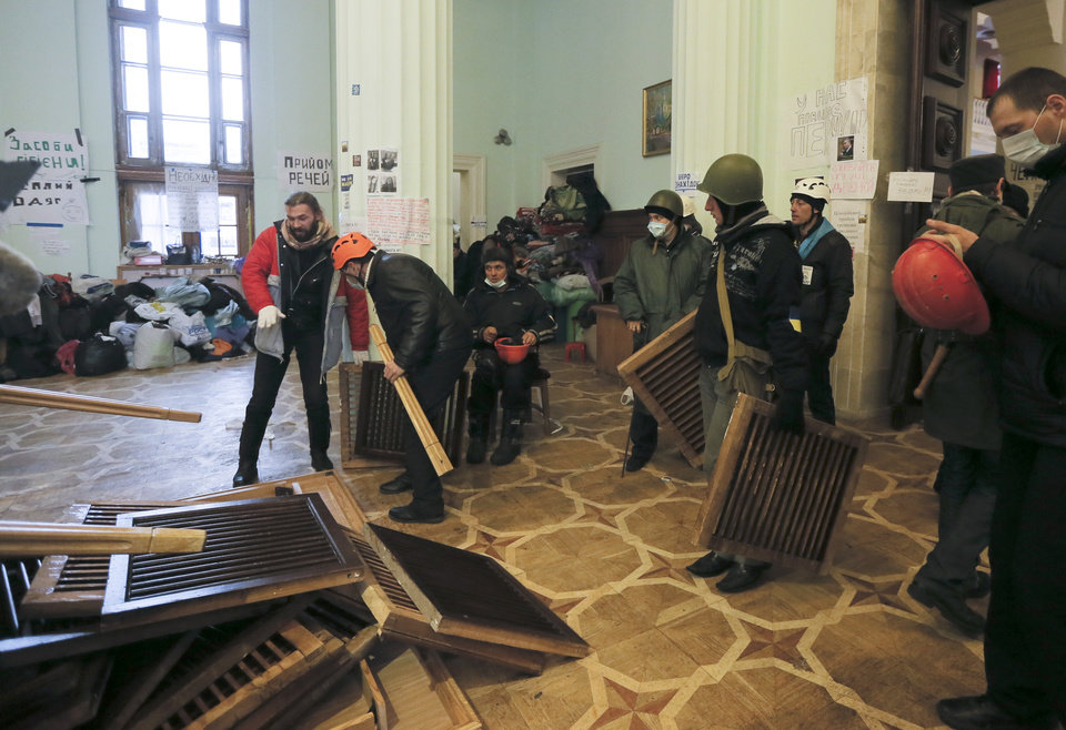 Photo - Pro Europe opposition activists armed with improvised weapons prepare for a police assault inside city hall in Kiev, Ukraine, Monday, Dec. 9, 2013. Hundreds of police in full riot gear on Monday flooded the center of Kiev key sites of mass anti-government protests that have gripped the capital for weeks, raising fears of a crackdown.(AP Photo/Efrem Lukatsky)