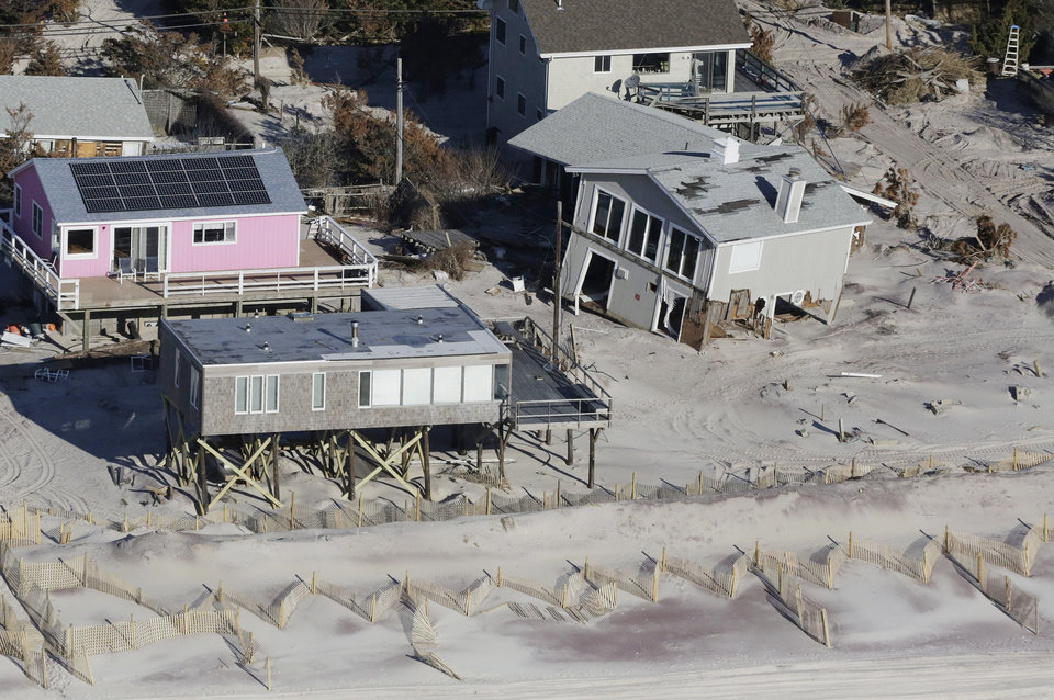 Photo - FILE - This Jan. 18, 2013 aerial file photo shows storm-damaged homes in Fire Island, N.Y. Sen. Charles Schumer (D-NY) said that the Sandy federal aid bill, scheduled for a vote Monday, Jan. 28, provides for more than $1 billion for projects to shield the coastline of New York City and Long Island. (AP Photo/Mark Lennihan, File)