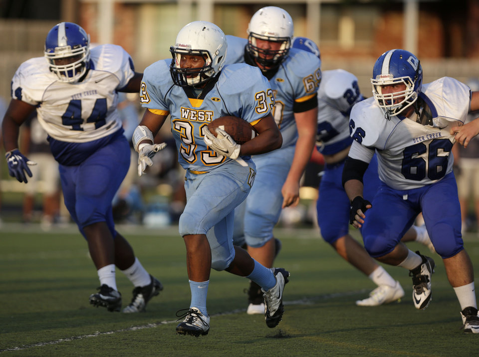Photo -                                        Above left:  Putnam City West's Terrell Tisdale runs the ball during a scrimmage Thursday against Deer Creek.                     Photo by Garett Fisbeck, For The Oklahoman                     Top right:  Tulsa Union's Lorenzo Thomas tries to tackle Westmoore's Bryson Lee during Thursday's scrimmage in Norman.                     Photo by Steve Sisney, The Oklahoman                     Above right:  Deer Creek's Tahj Davidson is taken down during a scrimmage Thursday against Norman North.                     Photo by Garett Fisbeck, For The Oklahoman                                     For coverage of Thursday night's scrimmages, see                     Page 8B .