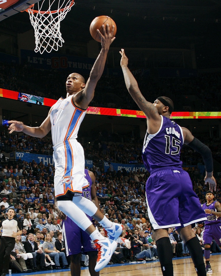 Oklahoma City's Russell Westbrook (0) takes the ball to the hoop past Sacramento's DeMarcus Cousins (15) during the NBA basketball game between the Oklahoma City Thunder and the Sacramento Kings at Chesapeake Energy Arena in Oklahoma City, Friday, April 13, 2012. Photo by Nate Billings, The Oklahoman