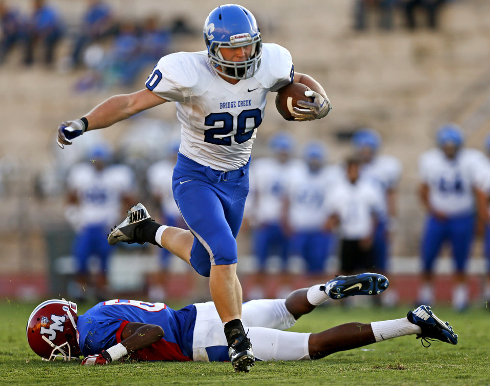 Bridge Creek's Morgan Merrell leaps past John Marshall's Jaden Manning  during a high school football game at Taft Stadium in Oklahoma City, Thursday, September 6, 2012. Photo by Bryan Terry, The Oklahoman