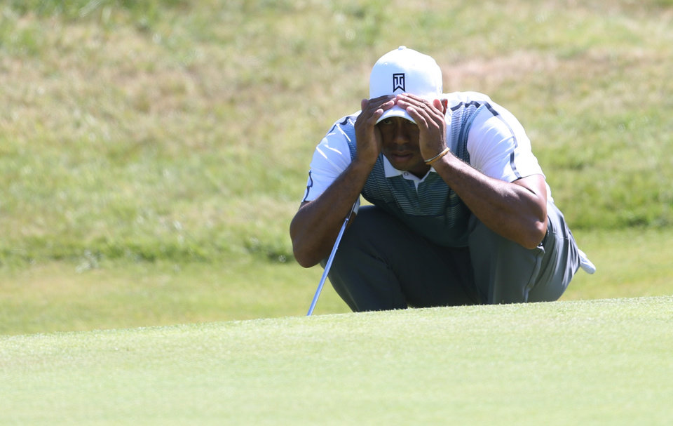 Photo - Tiger Woods of the US looks at his putt on the 9th green during the first day of the British Open Golf championship at the Royal Liverpool golf club, Hoylake, England, Thursday July 17, 2014. (AP Photo/Peter Morrison)