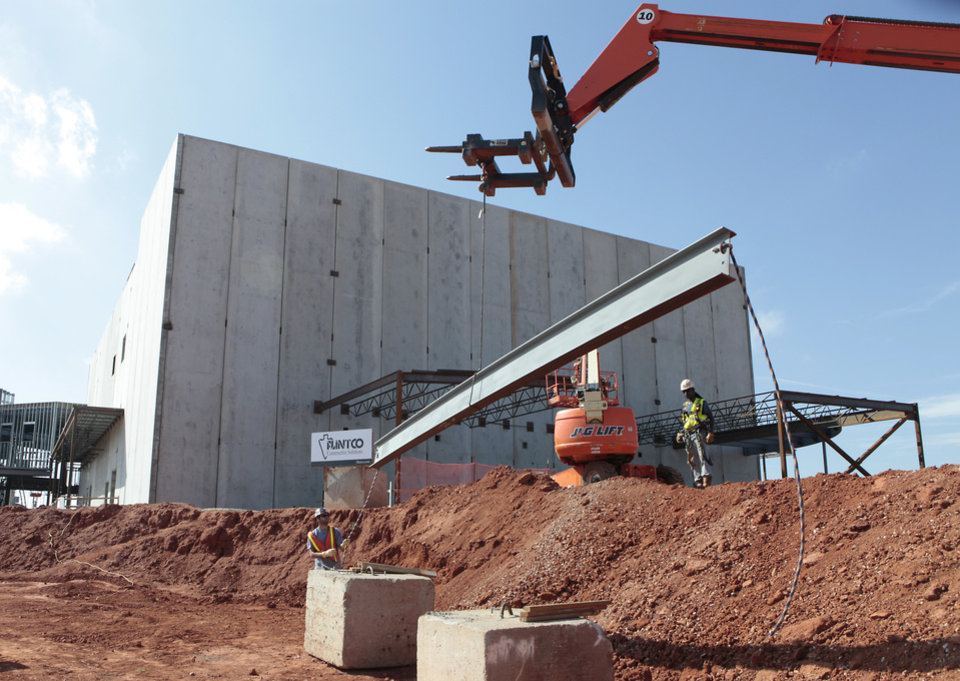 Photo - Oct. 23, 2012: Workers lift the last piece of structural steel during Deer Creek Public Schools' topping-out ceremony for the Deer Creek Performing Arts and Athletic Center. The 122,162-square-foot facility was to provide the district with 6A school facility space and additional room for athletics, band, choir, drama and orchestra facilities. [Photo By David McDaniel, The Oklahoman Archives]