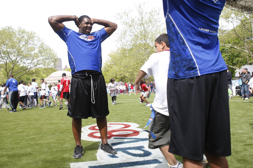 Photo - FORMER OSU / OKLAHOMA STATE UNIVERSITY / COLLEGE FOOTBALL PLAYER: NFL draft prospect Russell Okung, left, of Oklahoma State, watches youngsters run drills during a youth football clinic at Central Park in New York, Wednesday, April 21, 2010.  (AP Photo/Seth Wenig) ORG XMIT: NYSW114