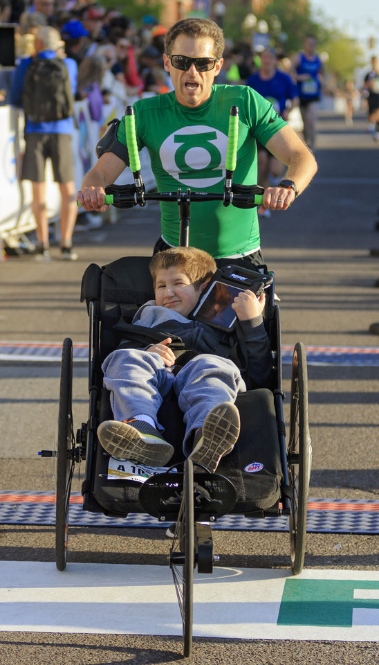 Photo -  Erik Heine pushes his son Stephen across the half-marathon finish line during Sunday's Oklahoma City Memorial Marathon. [PHOTO BY CHRIS LANDSBERGER, THE OKLAHOMAN]
