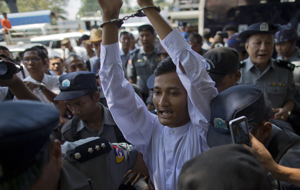 Photo - In this April 9, 2013 photo, a phalanx of police push Ye Min Oo, in handcuffs, through a crowd outside the district courthouse in Yangon, Myanmar. Plainclothes police seized the 969 supporter and student activist on the night of March 25, 2013, accusing him for inciting violence against Muslims and supporting extremist monks, including Wirathu. (AP Photo/Gemunu Amarasinghe)