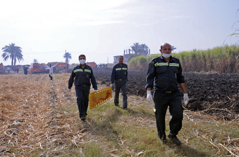 Photo - Rescue workers prepare to remove a body from the scene of a balloon crash outside al-Dhabaa village, just west of the city of Luxor, 510 kilometers (320 miles) south of Cairo, Egypt, Tuesday, Feb. 26, 2013. A hot air balloon flying over Egypt's ancient city of Luxor caught fire and crashed into a sugar cane field on Tuesday, killing at least 18 foreign tourists, a security official said. The casualties included French, British, Belgian, Hungarian, Japanese nationals and nine tourists from Hong Kong, Luxor Governor, Saad told reporters. (AP Photo/Hagag Salama)