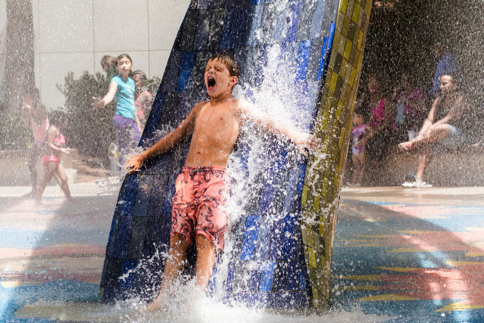 Photo - Michael McNanus, 7, screams as water pours down his back at the Myriad Botanical Gardens kids area fountain in Oklahoma City, Thursday, July 19, 2018. Photo by Anya Magnuson/The Oklahoman