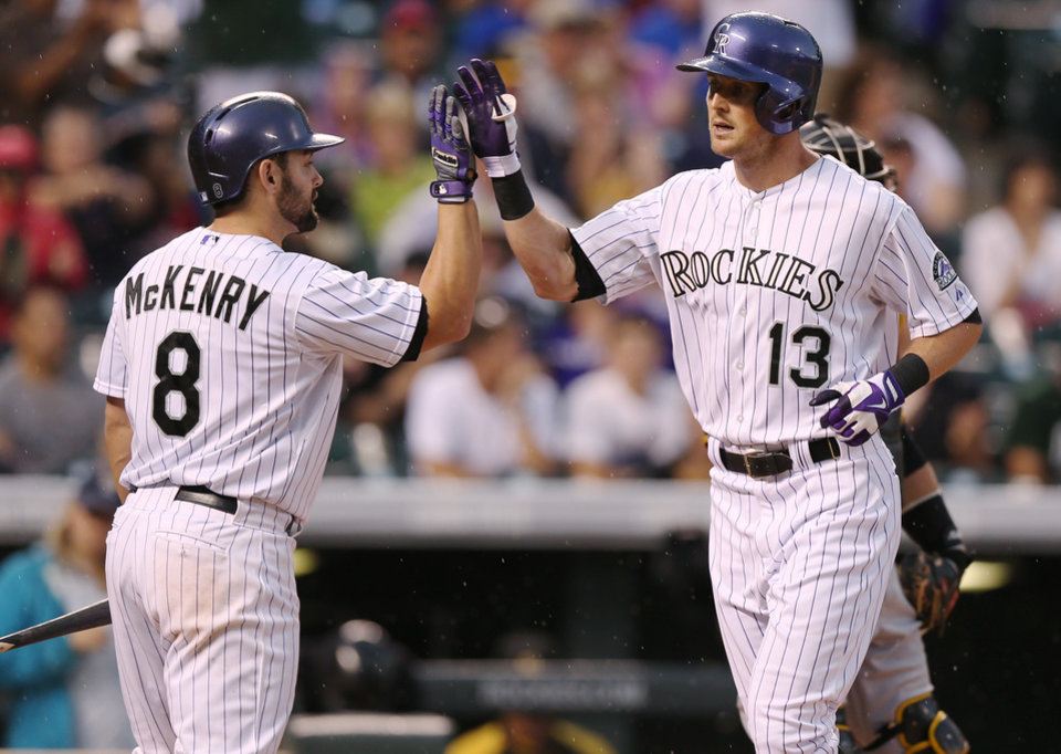 Photo - Colorado Rockies' catcher Michael McKenry, left, congratulates teammate Drew Stubbs who crosses home plate after hitting a solo home run against the Pittsburgh Pirates in the fourth inning of a baseball game in Denver, Saturday, July 26, 2014. (AP Photo/David Zalubowski)