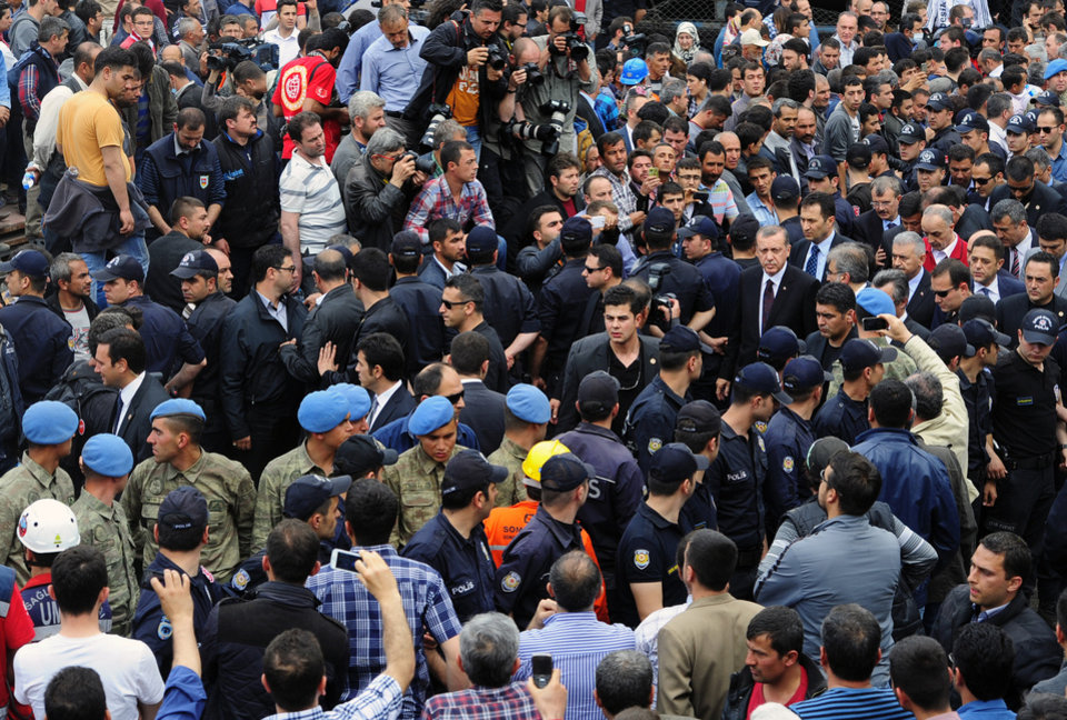 Photo - Turkey's Prime Minister Recep Tayyip Erdogan, center right, is surrounded by security members as he visits the coal mine in Soma, Turkey, Wednesday, May 14, 2014.  An explosion and fire at the coal mine killed at least 232 workers, authorities said, in one of the worst mining disasters in Turkish history. Turkey's Energy Minister Taner Yildiz said 787 people were inside the coal mine at the time of the accident. (AP Photo/Emre Tazegul)