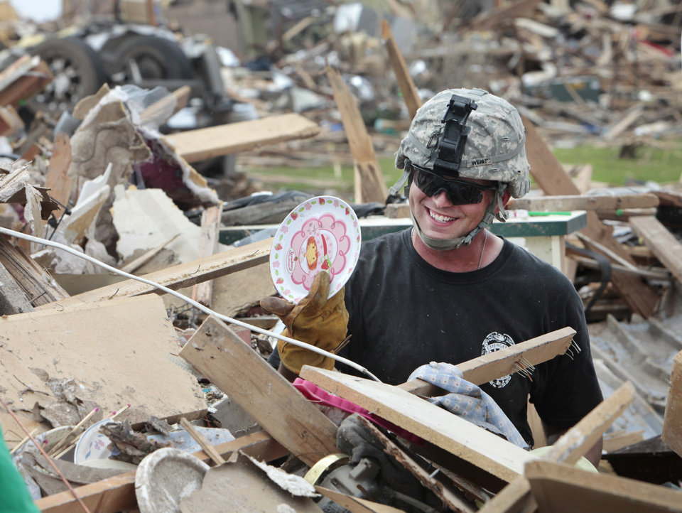 Specialist Bryan Weist, from Ft. Riley, Kansas, grins a he hold up a Strawberry Shortcake plate he found at the bottom of a pile at the home of Kim and Virgle Bell on south Broadway in the Westmoor addition, Sunday, May 26, 2013. Photo by David McDaniel, The Oklahoman