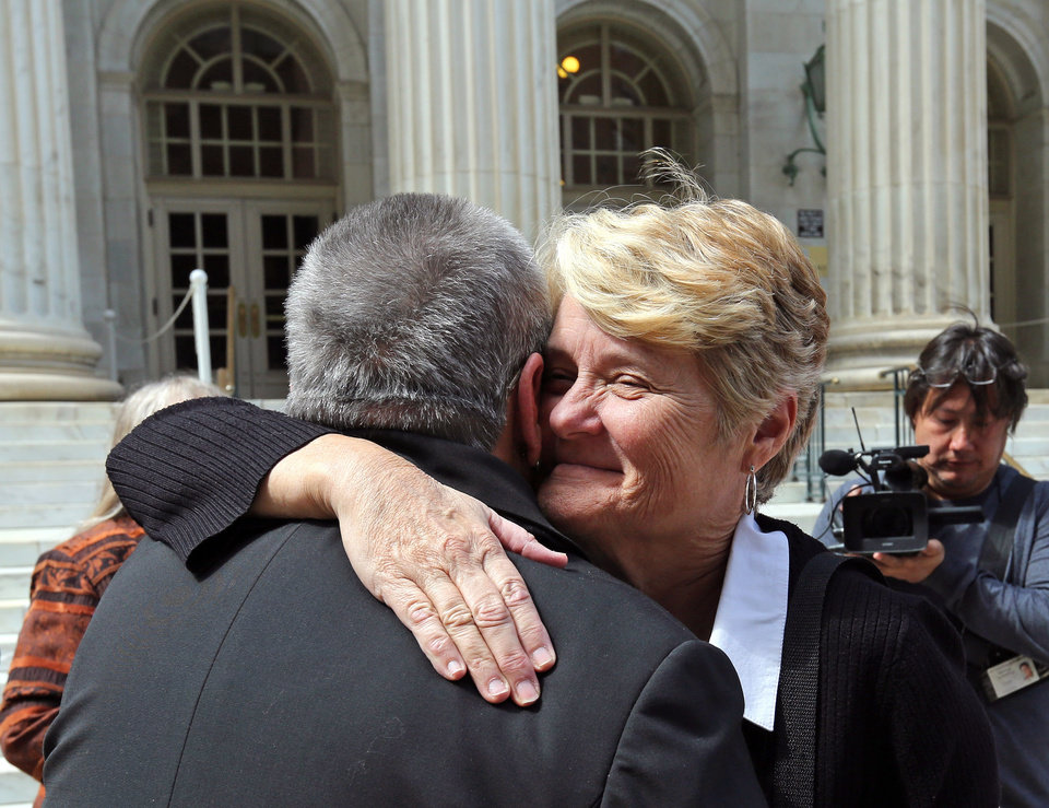 Photo - Plaintiff challenging Oklahoma's gay marriage ban Sue Barton, left, gets a hug from her pastor, Tulsa based Reverend Leslie Penrose, of the United Church of Christ, after leaving court following a hearing at the 10th U.S. Circuit Court of Appeals in Denver, Thursday, April 17, 2014. The appeal of a lower court's January ruling that struck down Oklahoma's gay marriage ban is the second time the issue has reached appellate courts since the U.S. Supreme Court shook up the legal landscape last year by finding the federal Defense of Marriage Act was unconstitutional. (AP Photo/Brennan Linsley)