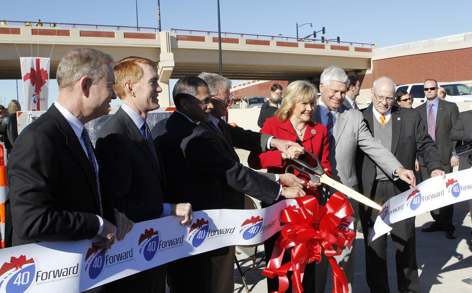Gov. Mary Fallin, center, with a pair of large scissors cutting the ribbon during grand opening ceremonies for the east bound lanes of the I-40 Crosstown in Oklahoma City Thursday, Jan. 5, 2012. Photo by Paul B. Southerland, The Oklahoman