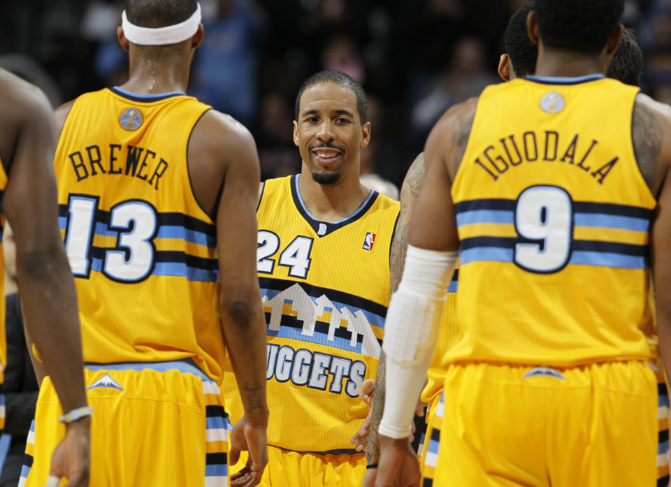 Denver Nuggets guard Andre Miller, center, congratulates teammates Corey Brewer, left, and Andre Iguodala as the Nuggets head into a timeout against the Oklahoma City Thunder in overtime of an NBA basketball game in Denver on Sunday, Jan. 20, 2013. The Nuggets won 121-118 in overtime. (AP Photo/David Zalubowski)