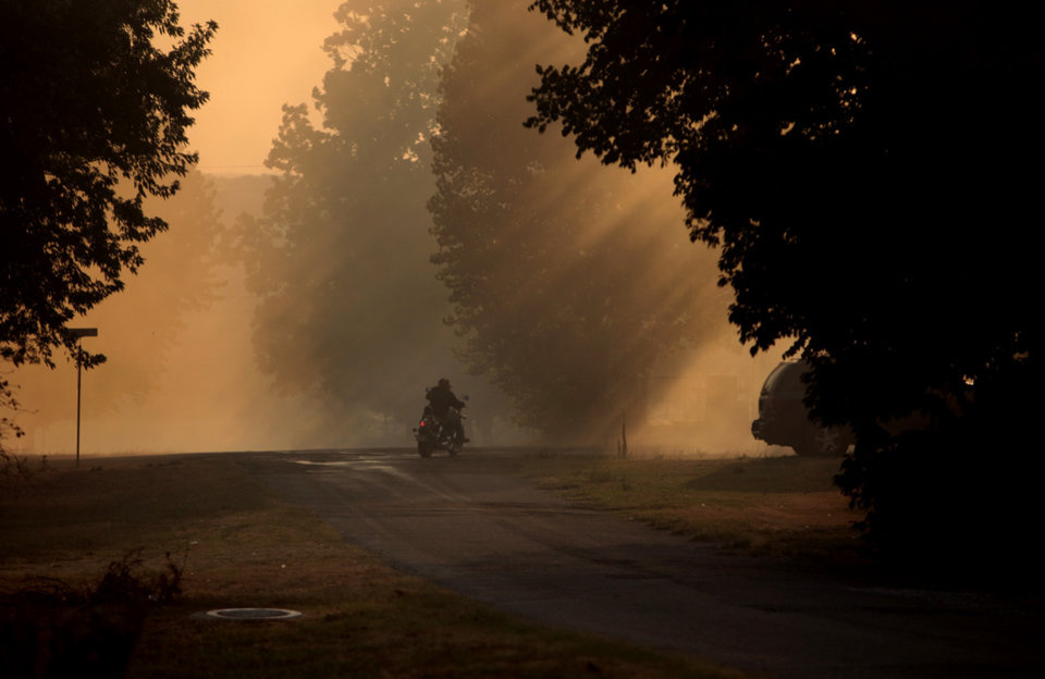 A motorcyclists drives through smoke during a large wildfire in Luther, Okla., Friday, Aug. 3, 2012. Photo by Sarah Phipps, The Oklahoman