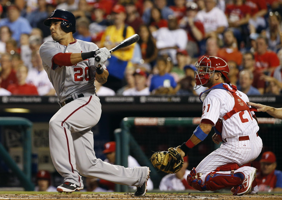 Photo - Washington Nationals' Ian Desmond, left, follows through after follows through after hitting an RBI-single off Philadelphia Phillies starting pitcher Kyle Kendrick during the first inning of a baseball game, Wednesday, Aug. 27, 2014, in Philadelphia. At right is catcher Wil Nieves. (AP Photo/Matt Slocum)