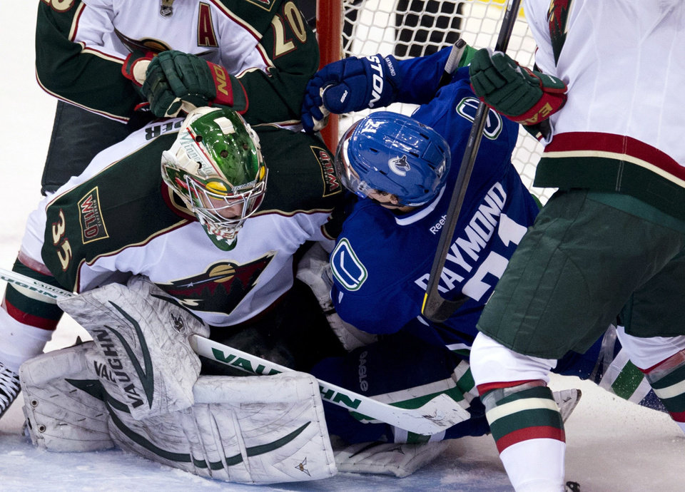 Vancouver Canucks left wing Mason Raymond (21) crashes into Minnesota Wild goalie Darcy Kuemper (35) during the second period of an NHL hockey game, Tuesday, Feb. 12, 2013, in Vancouver, British Columbia. (AP Photo/The Canadian Press, Jonathan Hayward)