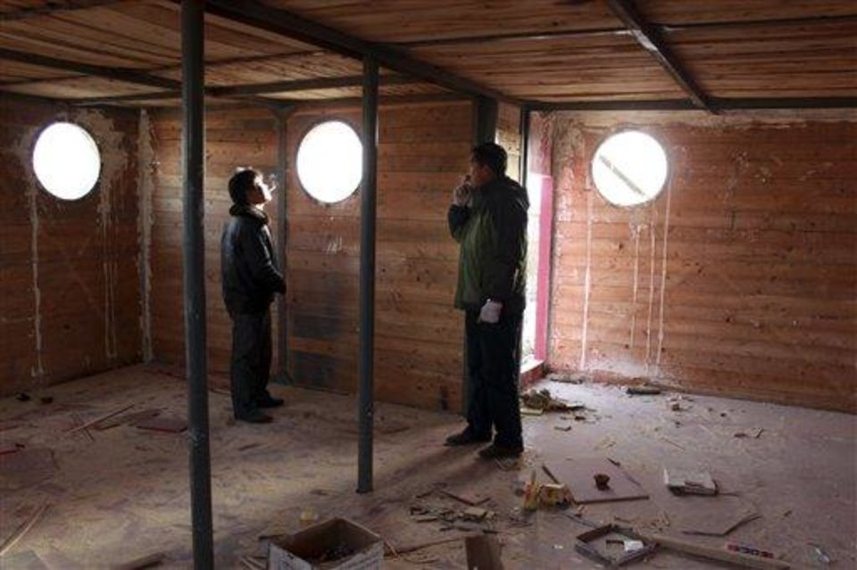 Photo - In this photo taken Nov. 24, 2012,  Lu Zhenghai, right, stands inside his ark-like vessel under construction in China's northwest Xinjiang Uyghur Autonomous Region. Lu Zhenghai is one of at least two men in China predicting a world-ending flood, come Dec. 21, the fateful day many believe the Maya set as the conclusion of their 5,125-year long-count calendar. Zhenghai has spent his life savings building the 70-foot-by-50-foot vessel powered by three diesel engines, according to state media. In Mexico's Mayan heartland, nobody is preparing for the end of the world; instead, they're bracing for a tsunami of spiritual visitors. (AP Photo/ANPF-Chen Jiansheng)