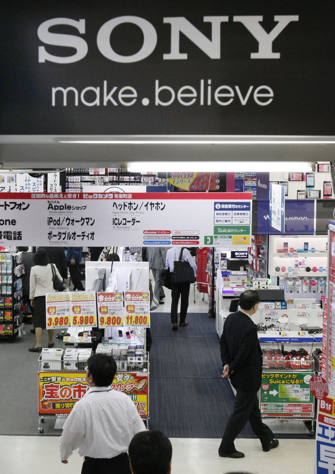 Photo - Shoppers look at an electronics store in Tokyo,Thursday, May 9, 2013. Sony Corp. is back in the black for the fiscal fourth quarter, recording a 93.9 billion yen ($948 million) profit, with big help from a weaker yen that boosts overseas earnings. (AP Photo/Koji Sasahara)