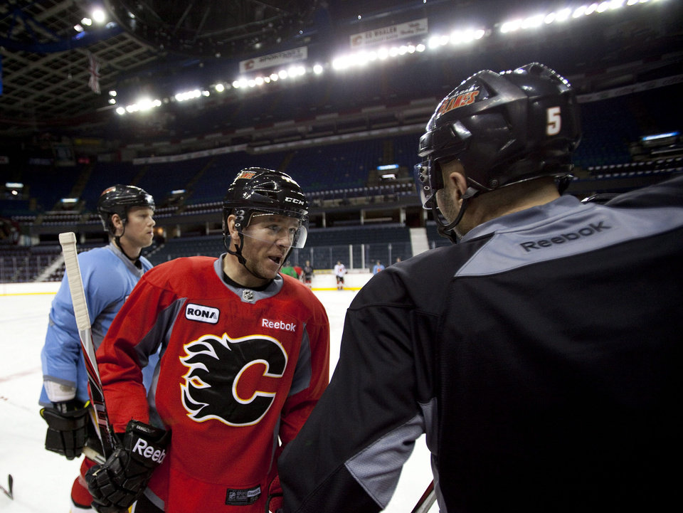 Calgary Flames' Alex Tanguay, center, talks with teammate Mark Giordano during NHL hockey training camp in Calgary,  Alberta, Monday, Jan. 14, 2013. (AP Photo/The Canadian Press, Jeff McIntosh)