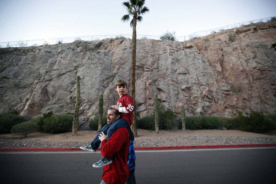 Photo - Craig Logsdon carries his son, Jude, 7, of Scottsdale, Ariz., walks toward the stadium before the Insight Bowl college football game between the University of Oklahoma (OU) Sooners and the Iowa Hawkeyes at Sun Devil Stadium in Tempe, Ariz., Friday, Dec. 30, 2011. Photo by Sarah Phipps, The Oklahoman