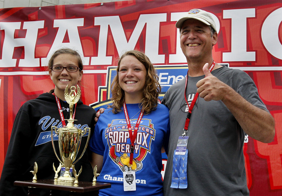 Melanie Kohout, center, of Geneva, Ill., Rally Masters winner, poses with her parents, Grace and Stan Inglehart, during the 76th All-American Soap Box Derby on Saturday, July 27, 2013, in Akron, Ohio. (AP Photo/Akron Beacon Journal, Paul Tople)