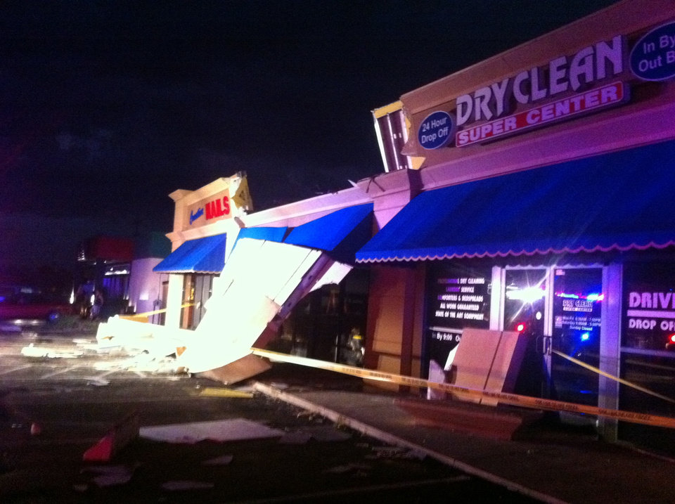 Photo - The upper part of the exterior wall of a yet-to-be opened liquor store called Mixed Delights collapsed and pinned the right leg of an ADT worker installing an alarm before emergency crews could cut him out near the corner of Briton and McArthur roads after a thunderstorm with high winds hit on Monday, August 8, 2011. Photo by Zach Gray/The Oklahoman