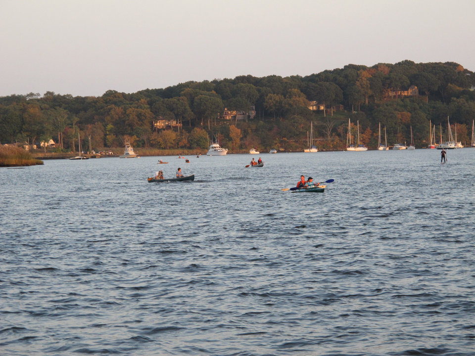 Photo - In this October 5, 2013 photo, boaters gather on the Connecticut River awaiting the arrival of tree swallows at sunset. In the fall, up to 400,000 swallows gather nightly over a remote island on the river, massing in the sky before plunging in a