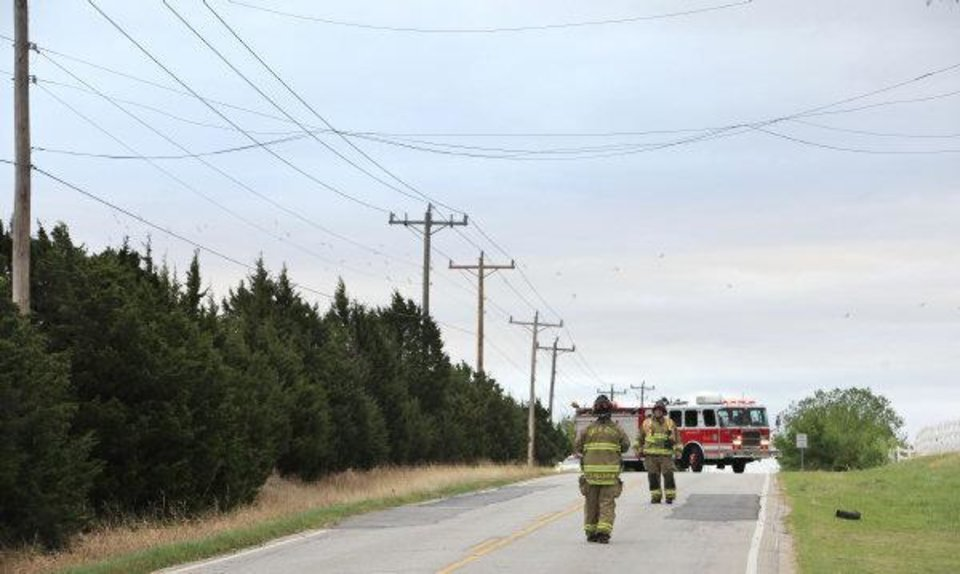 Photo - Oklahoma City firemen look at power lines dislodged by high winds today on Hefner Road just east of Kelley Ave. Photo by Paul B. Southerland  PAUL B. SOUTHERLAND