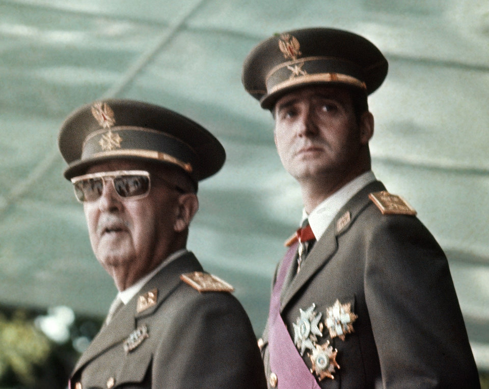 Photo - FILE This is a May 1973 file photo of Spain's leader Francisco Franco, left, with his future successor as King, Prince Juan Carlos de Borbon, as they watch a military parade in Madrid .  Spain's King Juan Carlos will abdicate and pave the way for his son, Crown Prince Felipe, to take over, Spanish Prime Minister Mariano Rajoy told the country Monday in an announcement broadcast nationwide. He did not say when Juan Carlos would abdicate because the government must now craft a law creating a legal mechanism for the abdication and for 46-year-old Felipe's assumption of power. King Juan Carlos came to power in 1975, two days after the death of longtime dictator Francisco Franco. He endeared himself to many Spaniards in large part by putting down an attempted military coup in 1981 when he was a young and largely untested head of state.  (AP Photo/File)