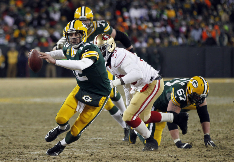 Photo - Green Bay Packers quarterback Aaron Rodgers (12) scrambles during the second half of an NFL wild-card playoff football game, Sunday, Jan. 5, 2014, in Green Bay, Wis. The 49ers won 23-20. (AP Photo/Mike Roemer)