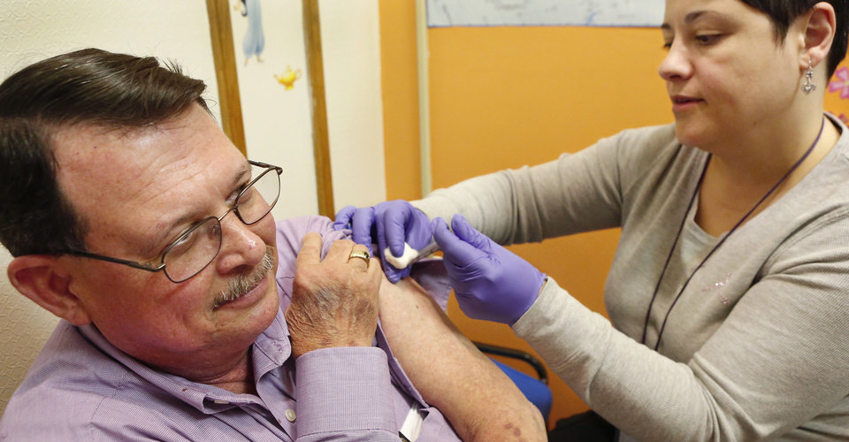 Photo -  Russ Calhoun, of Midwest City, receives a flu shot from registered nurse Hamideh Jedari at the Oklahoma City-County Health Department. PHOTO BY JIM BECKEL, OKLAHOMAN ARCHIVE    Jim Beckel -