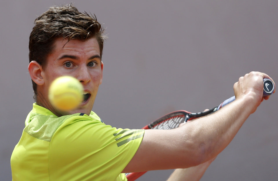 Photo - Austria's Dominic Thiem returns the ball to Spain's Rafael Nadal during their second round match of  the French Open tennis tournament at the Roland Garros stadium, in Paris, France, Thursday, May 29, 2014. (AP Photo/Darko Vojinovic)