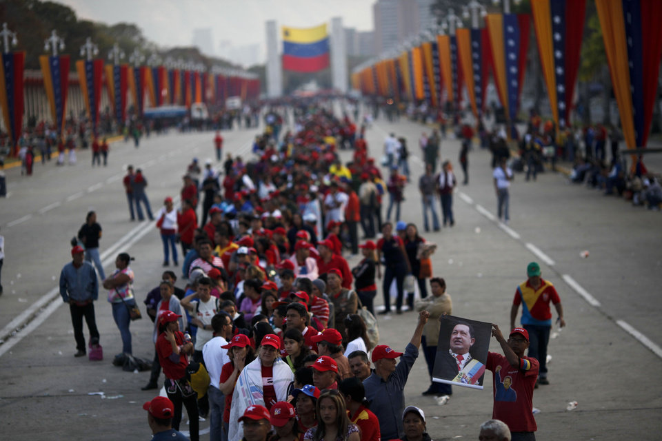 Photo - People line up to see the body of Venezuela's late President Hugo Chavez outside the military academy where he is lying in state in Caracas, Venezuela, Saturday, March 9, 2013. Chavez died on March 5, 2013 after a nearly two-year bout with cancer. He was 58. (AP Photo/Rodrigo Abd)